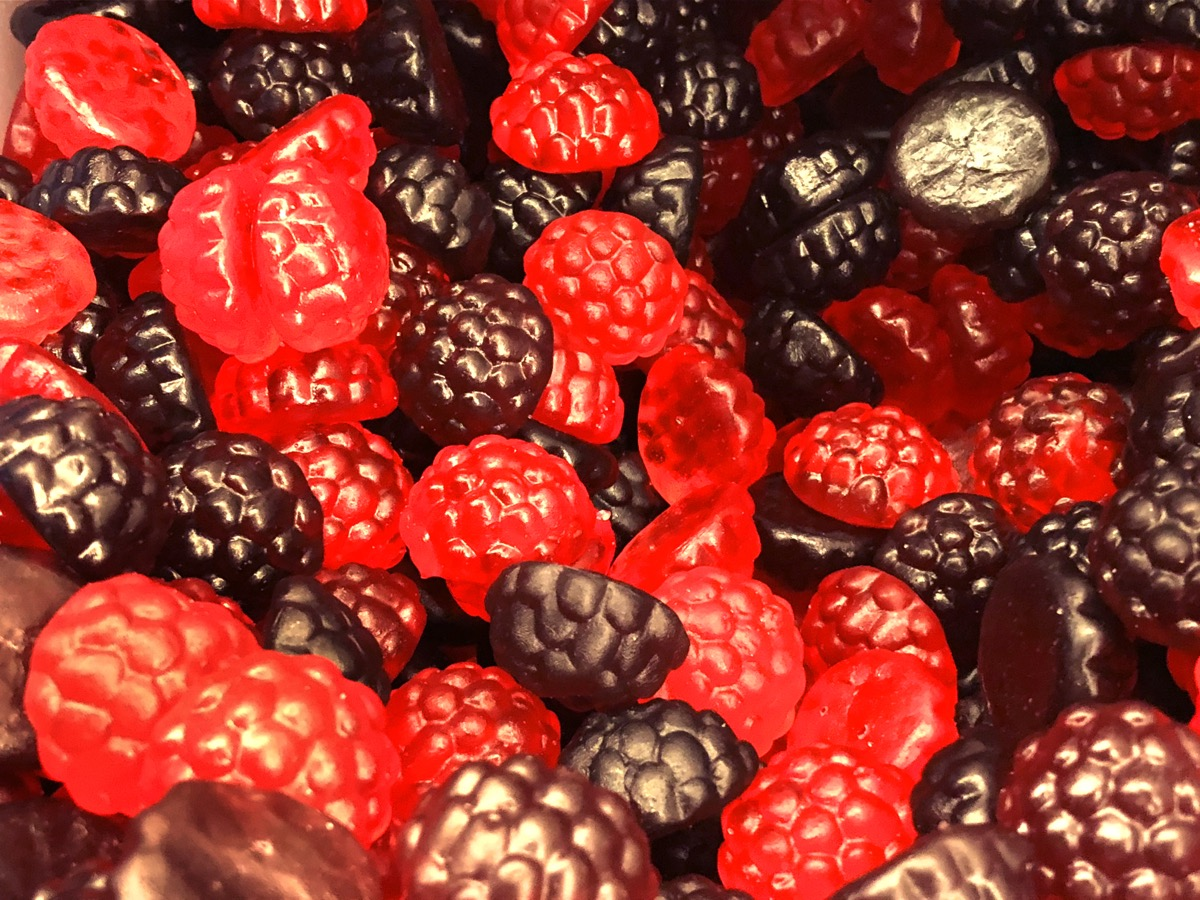 Stock photo of sweet shop pic and mix display of purple and red jelly sweet / gummy berry fruit shaped like blackberries and raspberries.