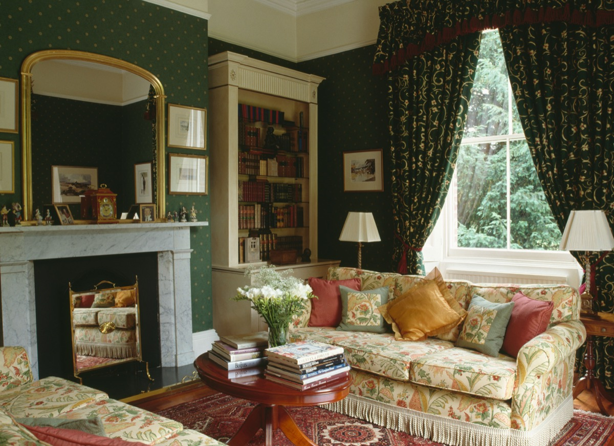 Gilt mirror above marble fireplace in nineties living room green wallpaper patterned curtains floral sofas