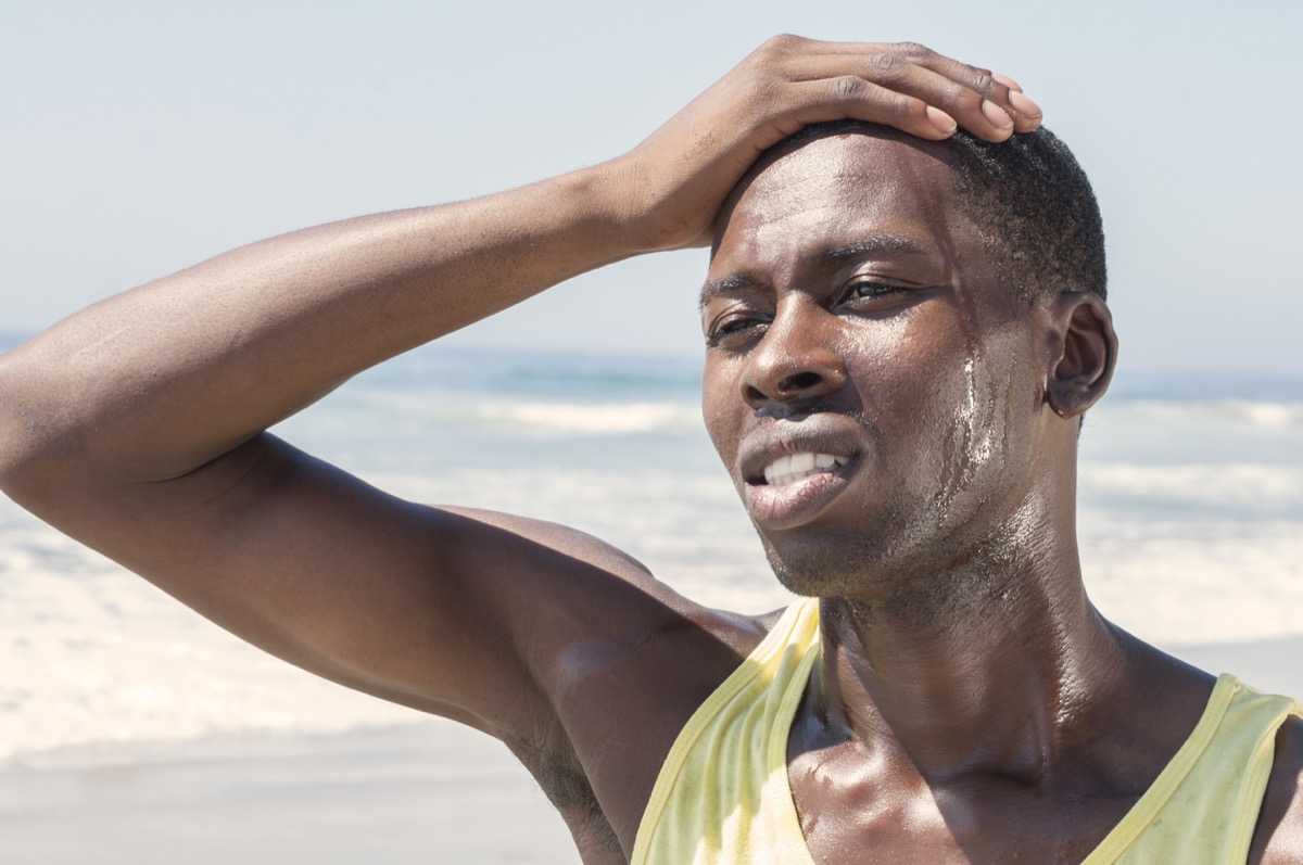 close up of black man sweating outside with his hand on his forehead