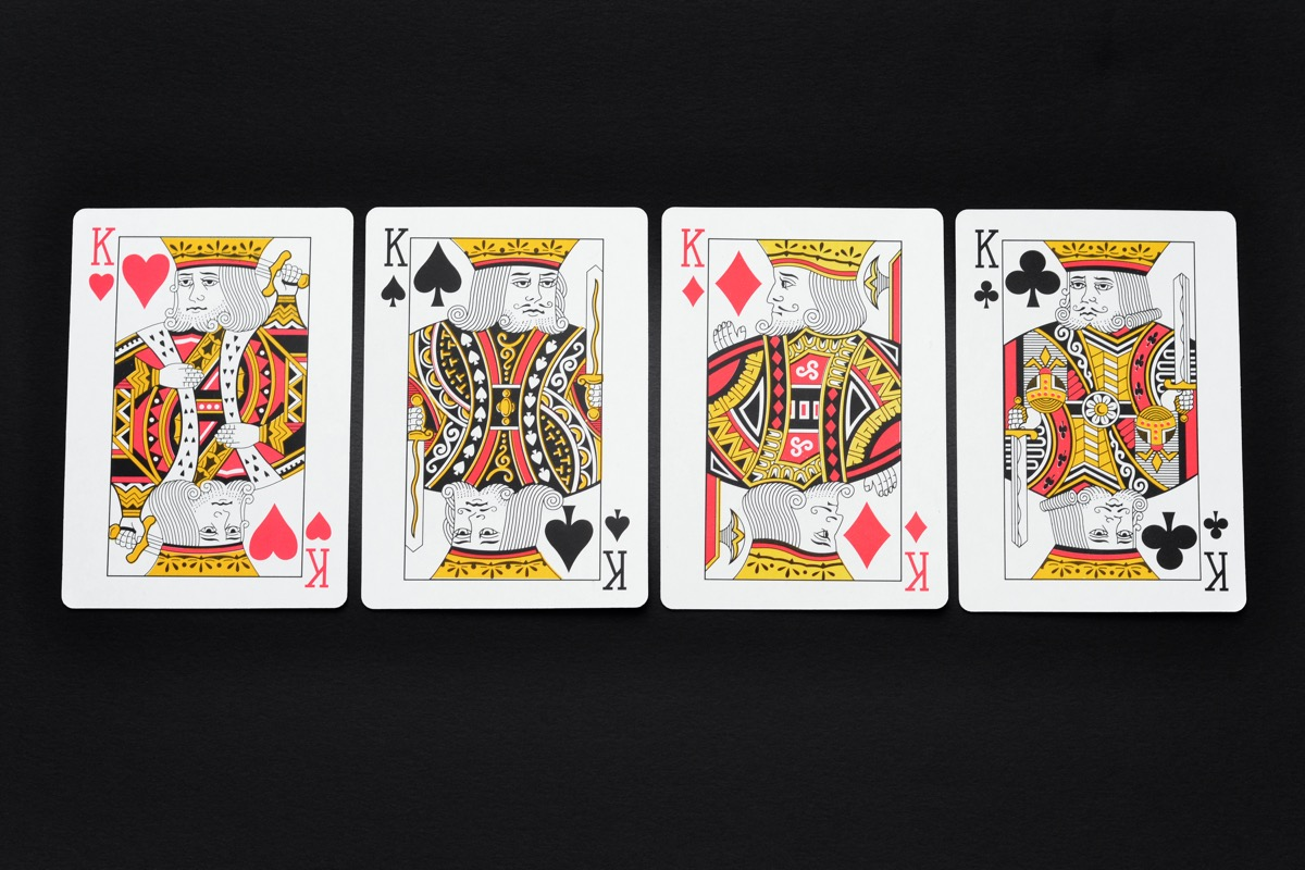Close up of the four kings in a deck of playing cards on a black background.
