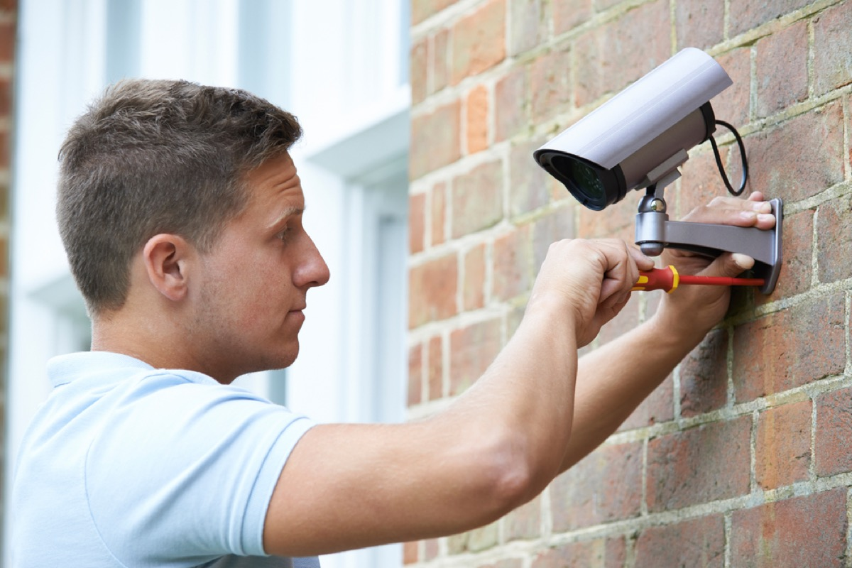 man installing security camera, bad home renovations