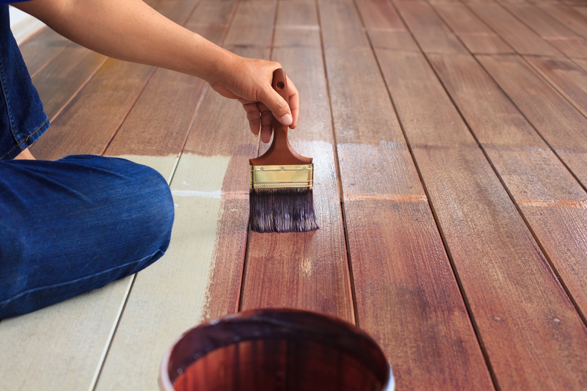 man painting floor with paintbrush