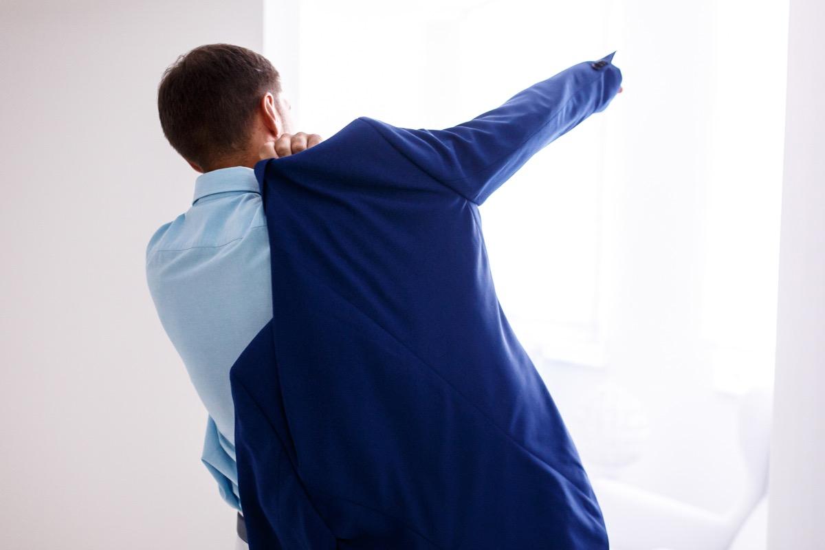 man putting arm through armscye in jacket
