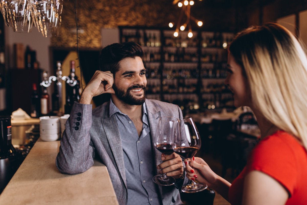 man and woman on a date drinking red wine