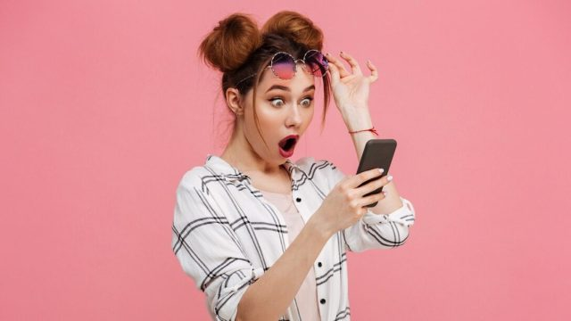 A shocked woman looking at a smartphone