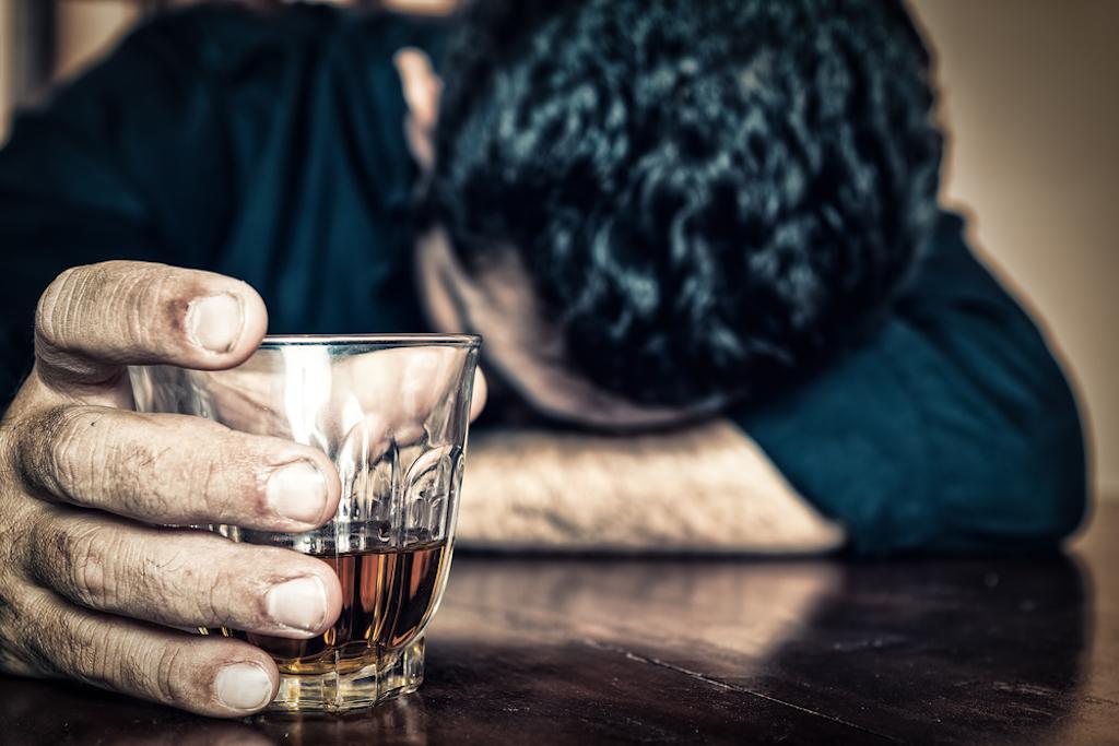 depressed man drinking whiskey
