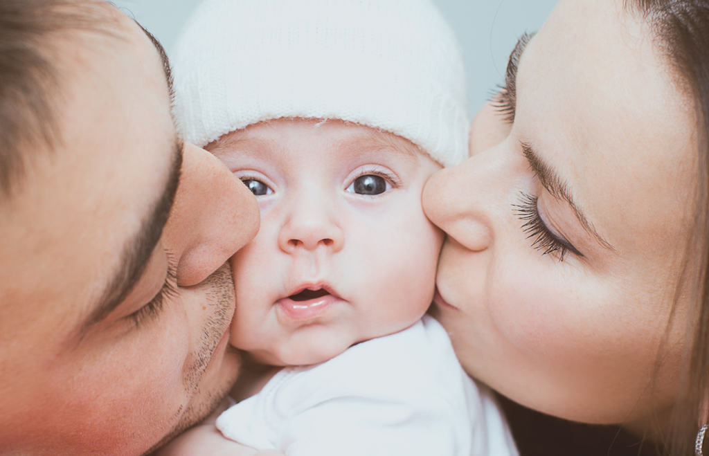 parents kissing baby, how parenting has changed