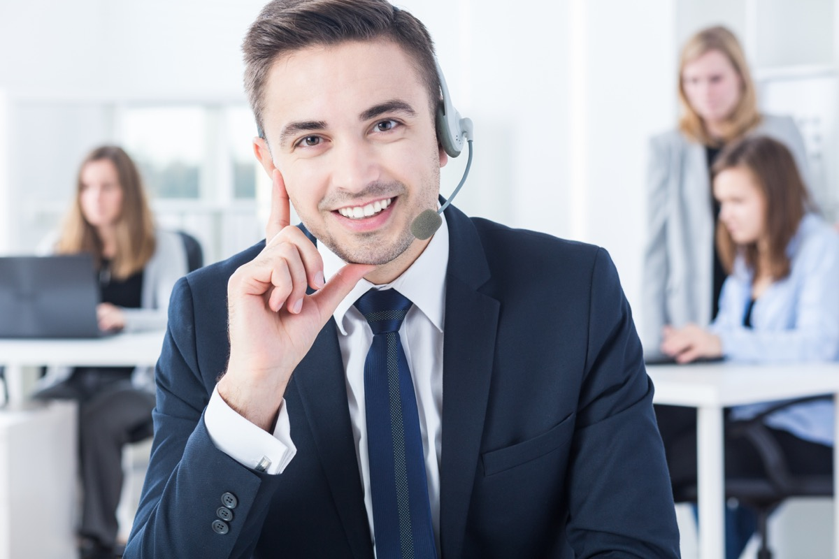 male telemarketer with headset smiles