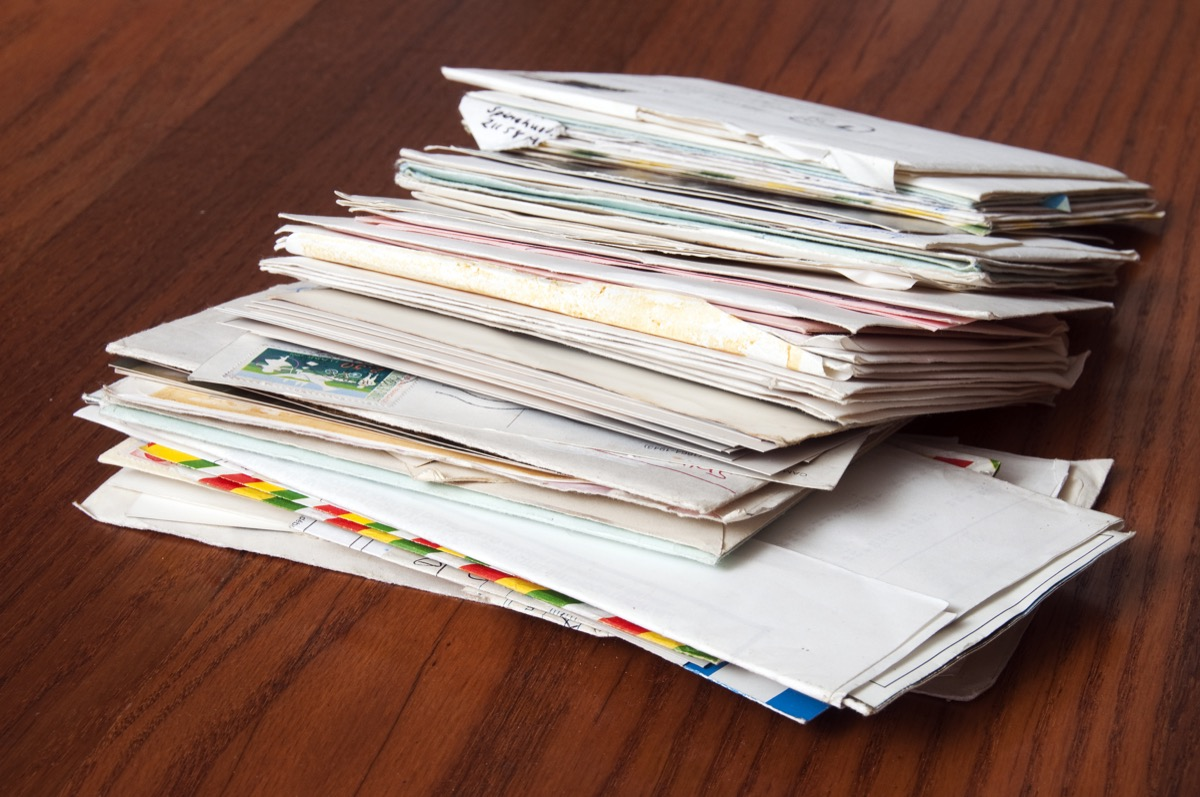 stack of mail and piles of paper, spam mail