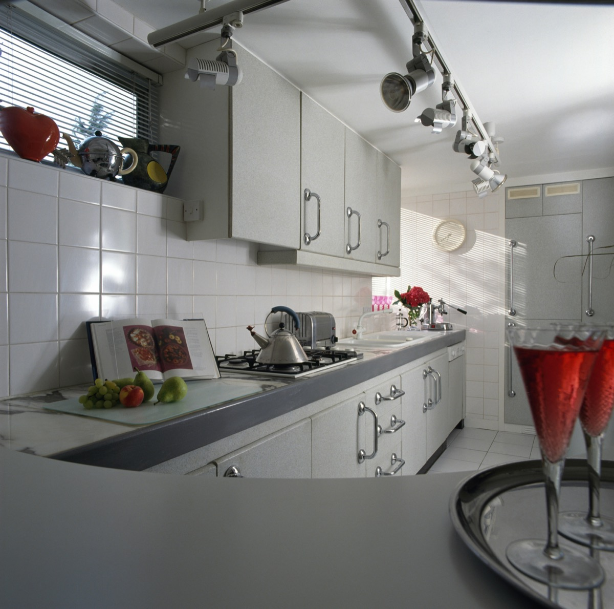 Track spotlights and white tiling in a nineties kitchen with pale gray fitted units and an Alessi kettle on the hob