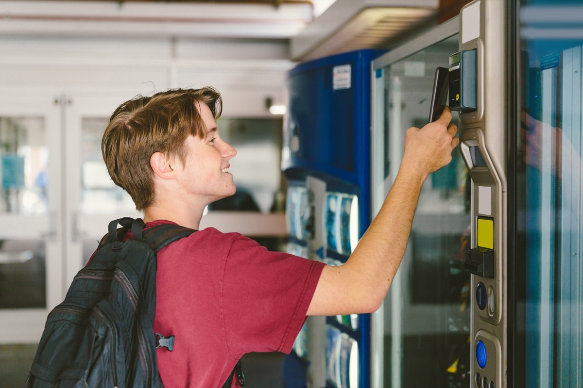 Student teenage boy wearing backpack uses mobile phone to pay for snack and drink at vending machine