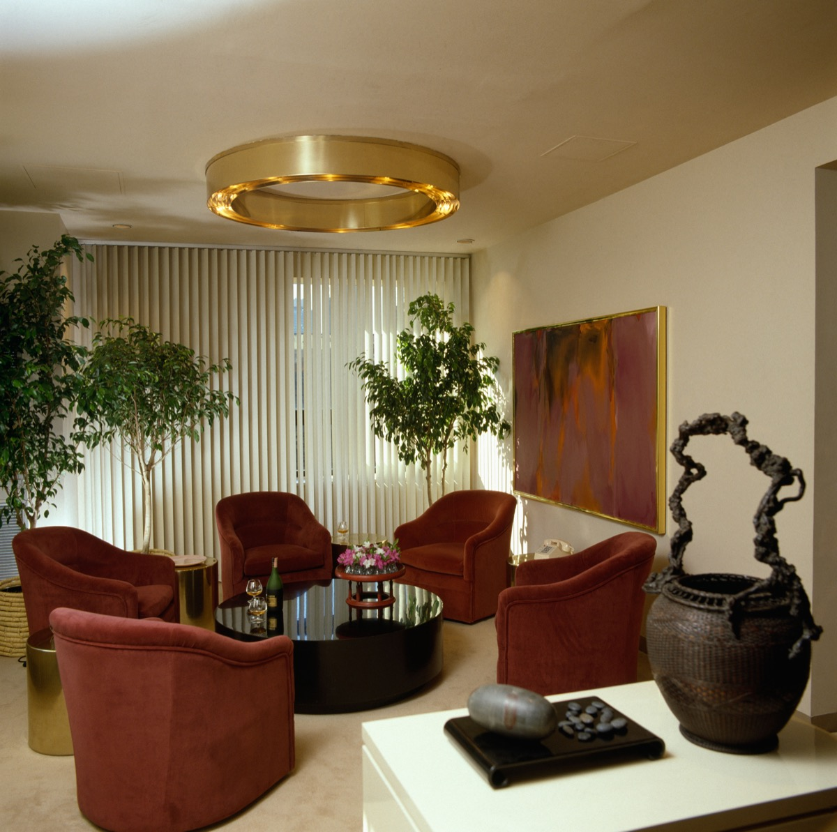 A9K1RP Circular metal light fitting in eighties livingroom with red velour sofas and vertical Venetian blinds
