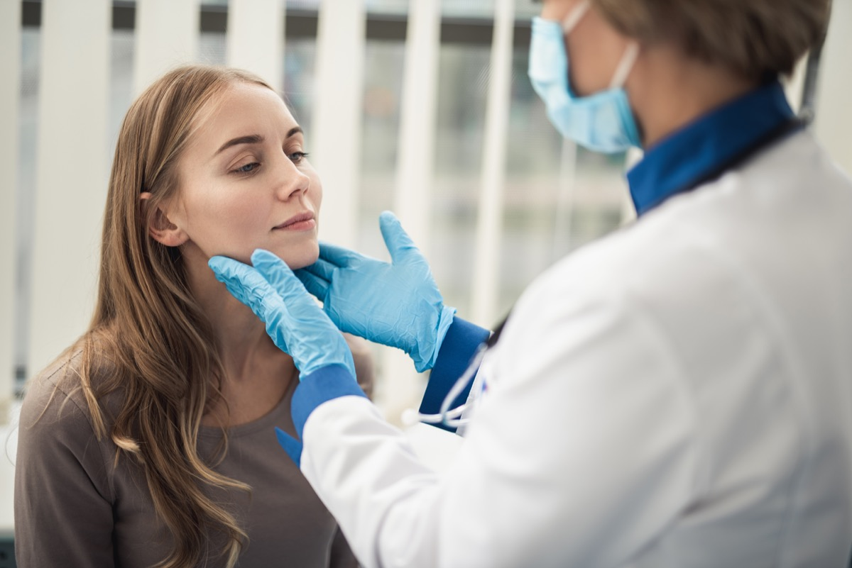 woman getting her tonsils checked by a doctor