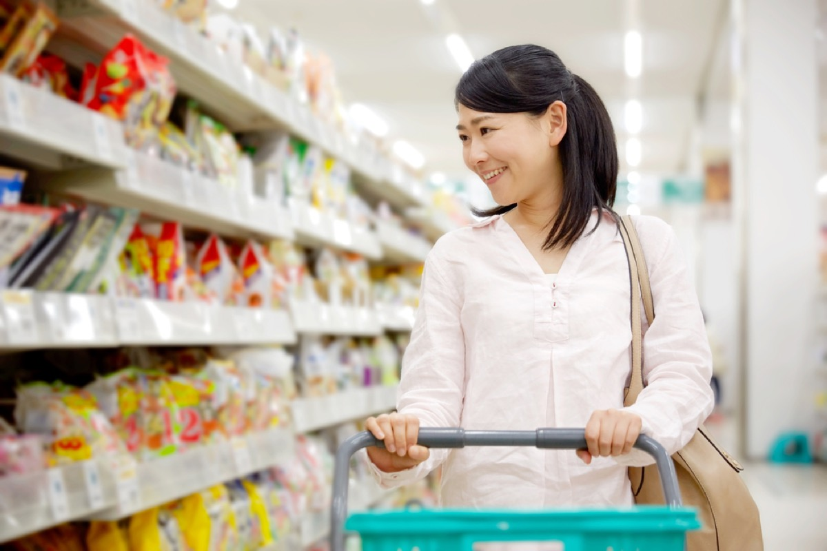 woman grocery shopping at supermarket, working mom