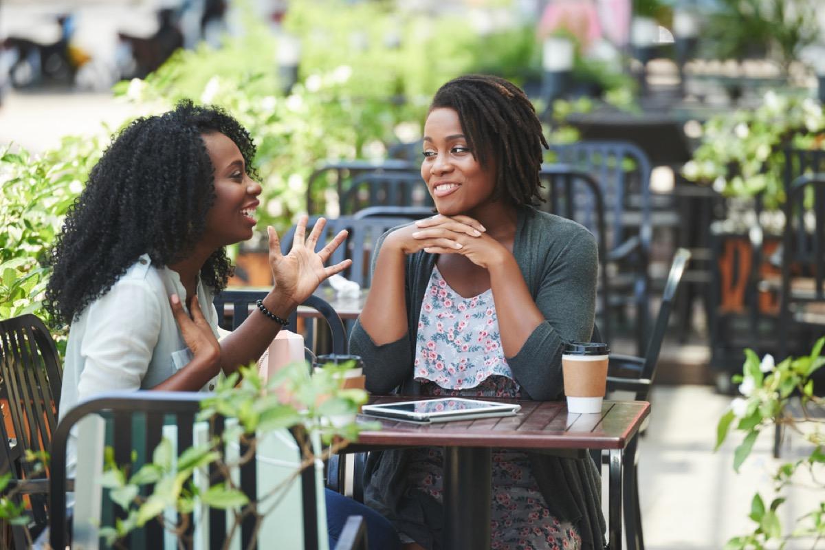 women talking in an outdoor courtyard, working mom