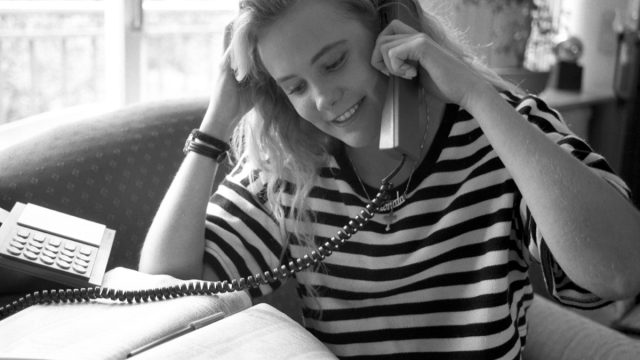 1980s photo of a woman calling someone to ask out, 1980s nostalgia