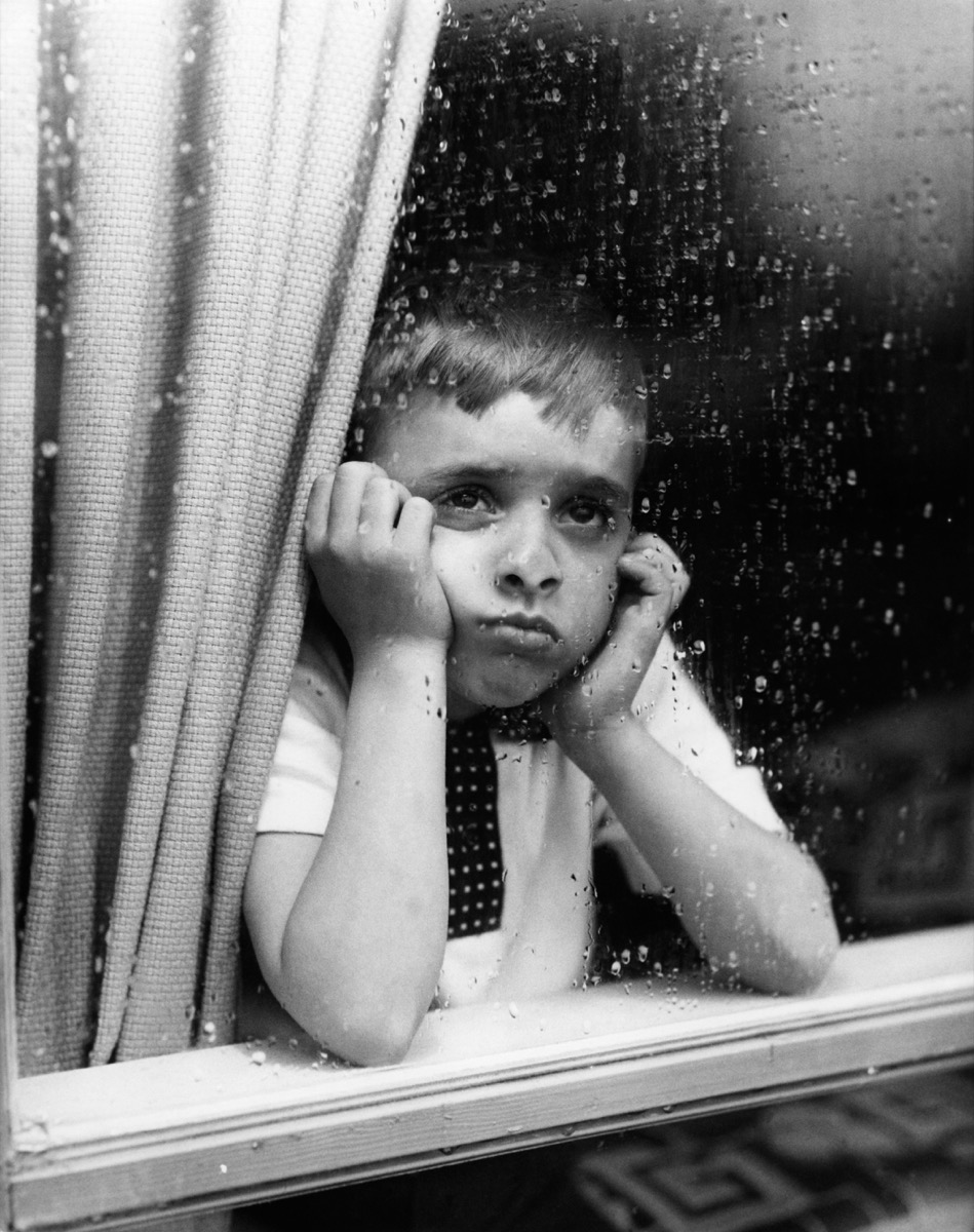 1950s sad boy looks out window with hands on chin, shows how different parenting was in the 1950s