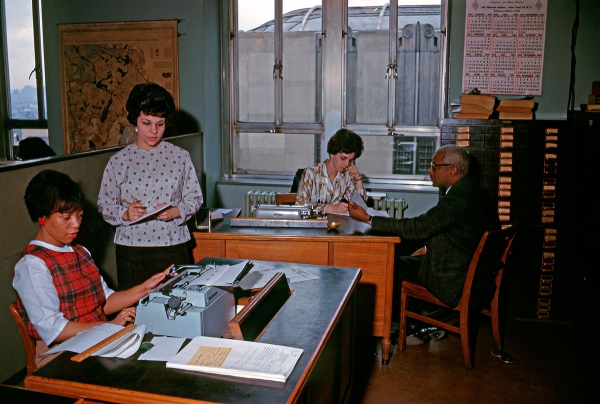 1960s black woman sits at typewriter in an office with three colleagues, shows how different parenting was in the 1950s