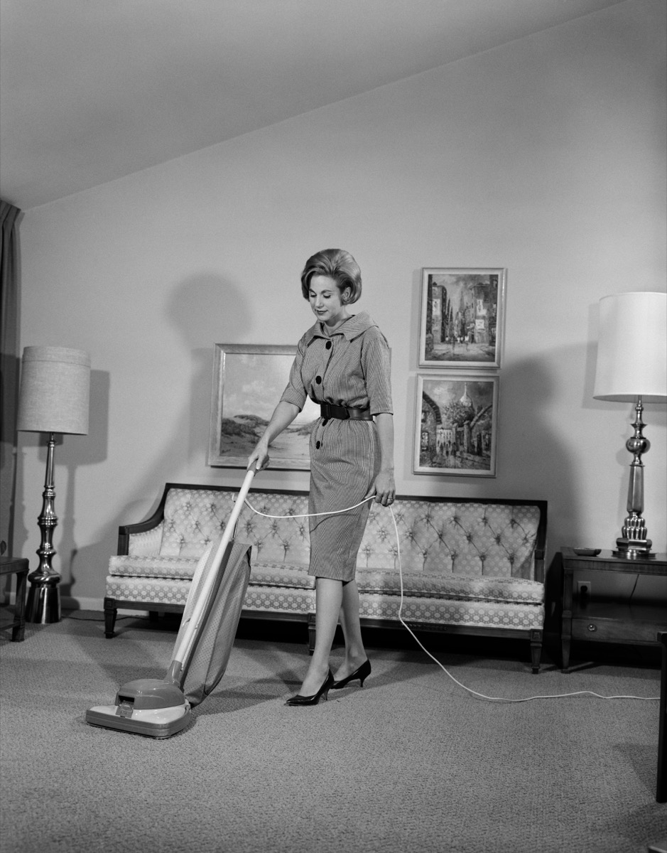 1960s white woman vacuums living room, shows how different parenting was in the 1950s