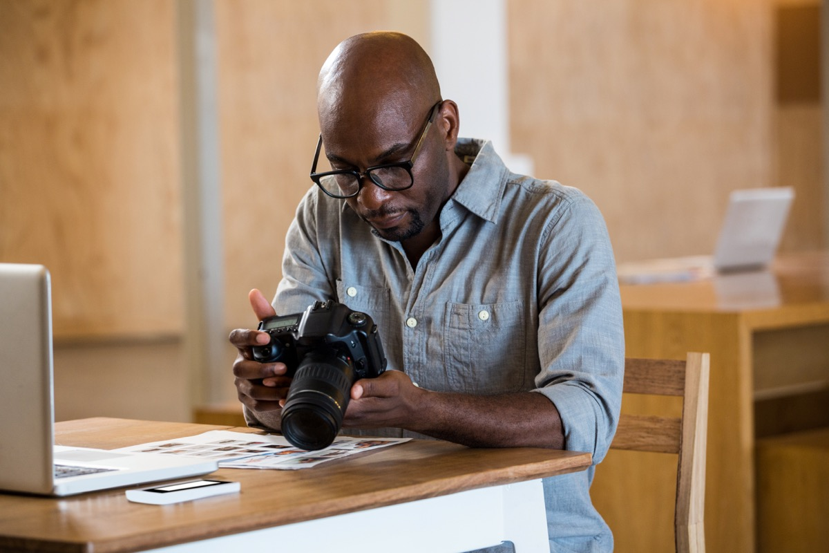 Black man in denim shirt with black glasses holds camera in front of computer