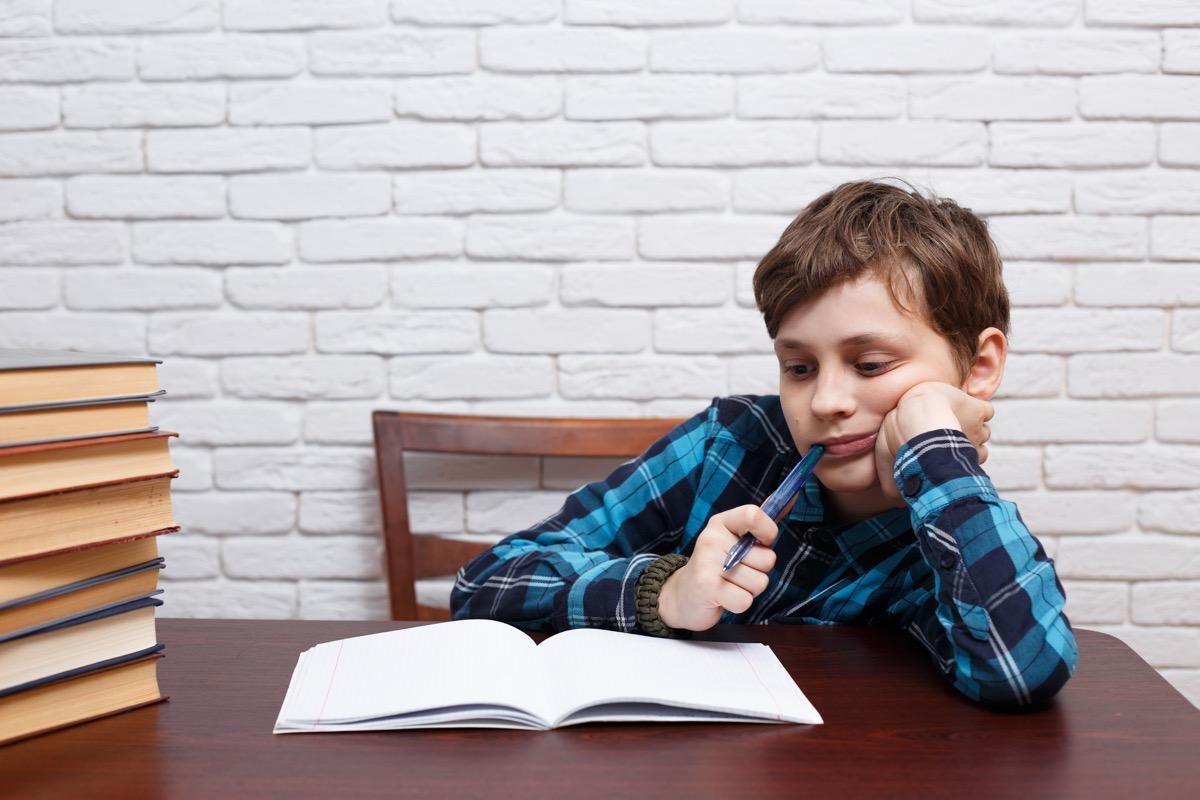 White boy chews pen cap at desk, bad child habit