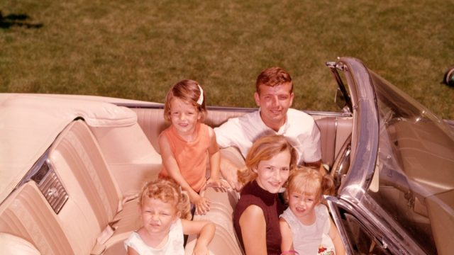 1960s white family with father, mother, daughter on lap in front seat, and two daughters in back seat, things that would horrify parents today