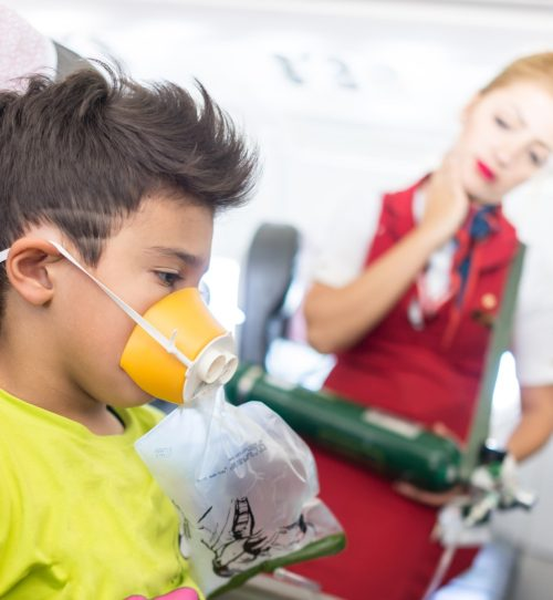 boy in airplane seat with oxygen mask as flight attendant looks on, annoyed flight attendant