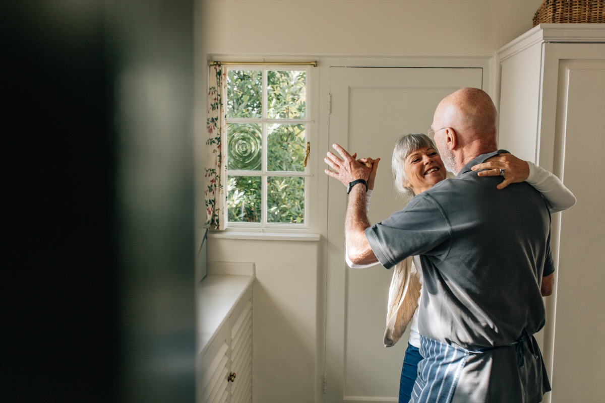 Mature couple dancing in their home