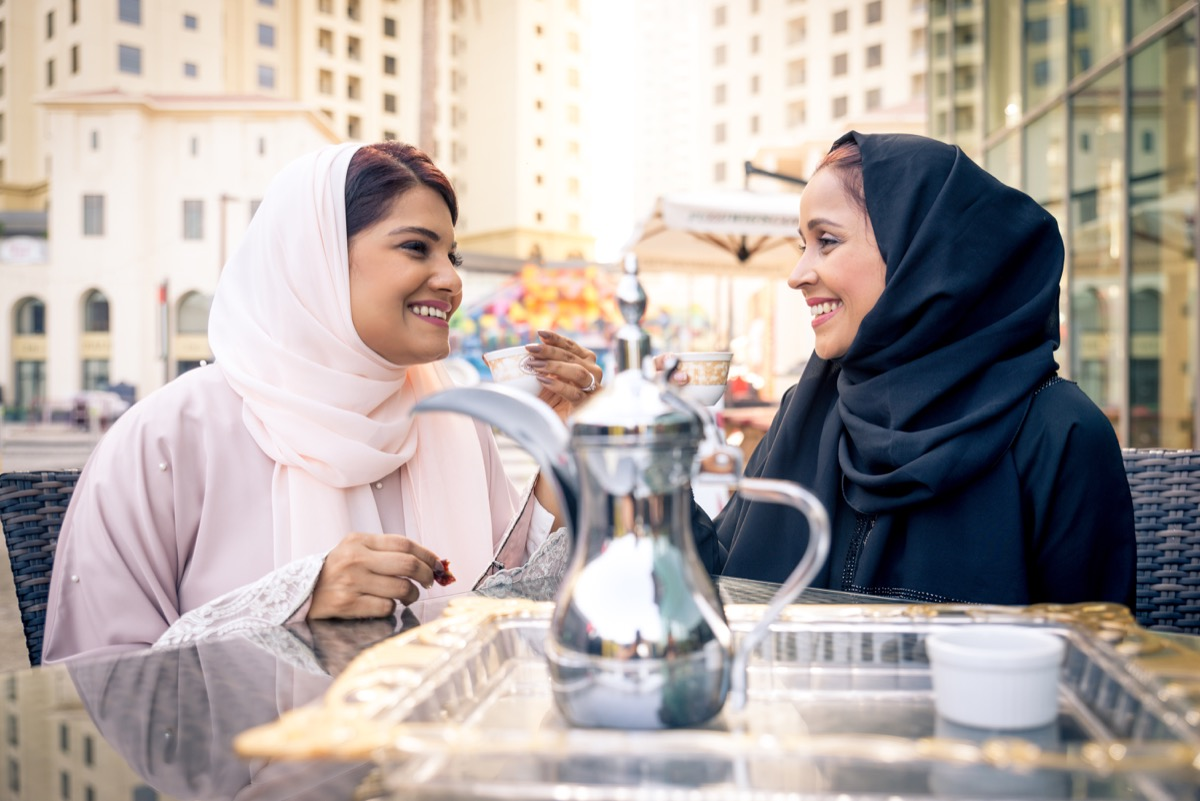 Two women wearing hijabs—one pink and one black—share tea outside