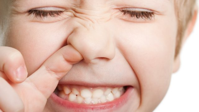 Closeup of young white boy picking his nose while smiling