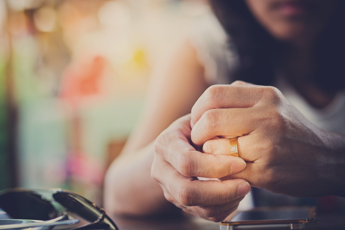 sad woman's hands clenched as she plays with wedding ring, married for money