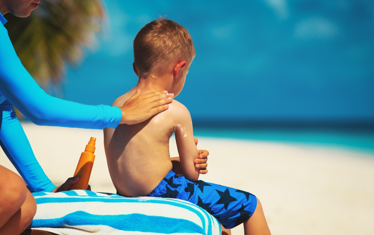 Mom applies sunscreen to child's back on beach, bad kid habits