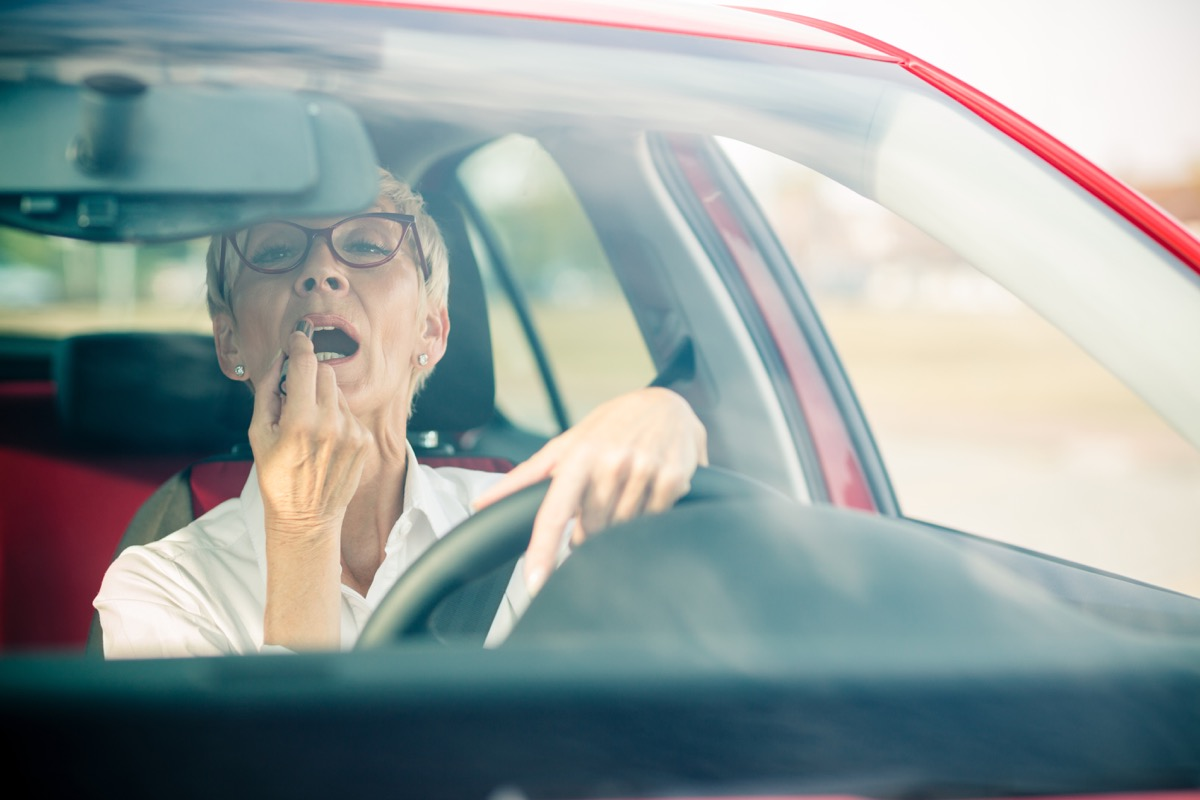 woman stopped at red light with short grey hair puts on lipstick