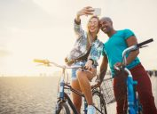attractive interracial couple on bikes taking selfie, make yourself more attractive
