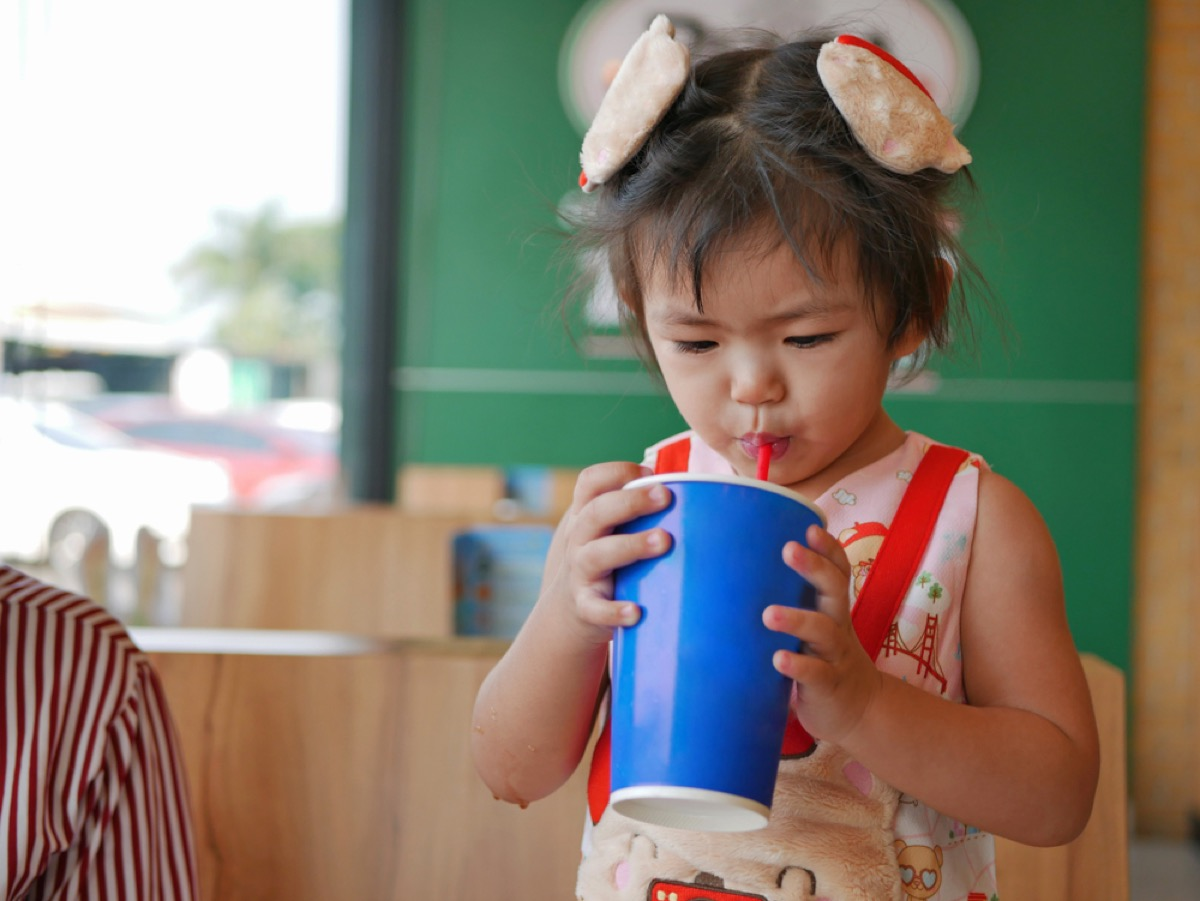 little girl drinking soda from cup with straw, bad parenting advice
