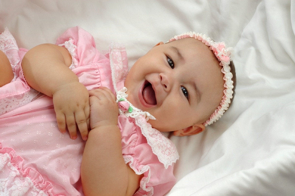 baby girl laughing in pink dress, ways parenting has changed.