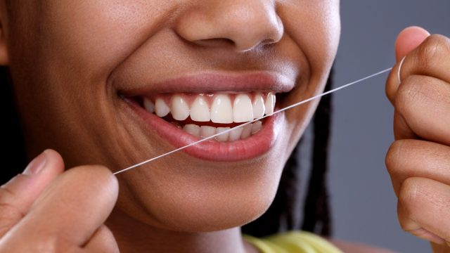 Black Woman Smiling and Flossing, subtle symptoms of serious disease