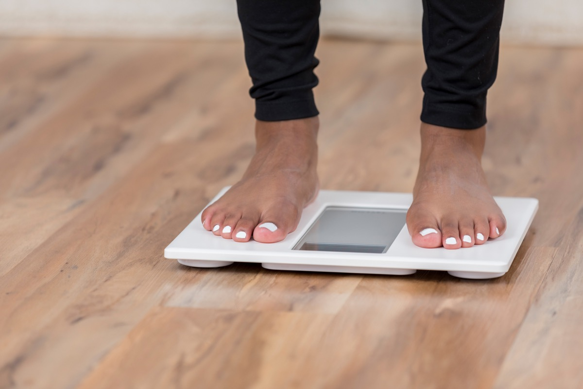 Woman weighing herself on a scale for potential weight loss or weight gain