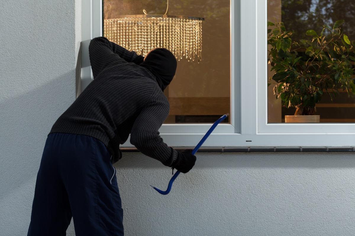 burglar getting ready to enter house through window, safety tips