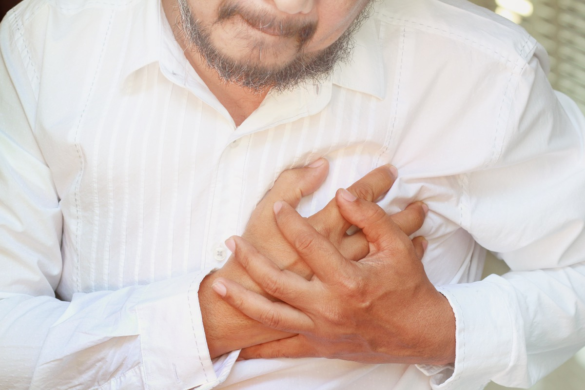 man holding his chest in pain, health questions after 40