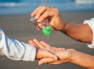 Mom Giving Her Child Hand Sanitizer on the Beach bad parenting