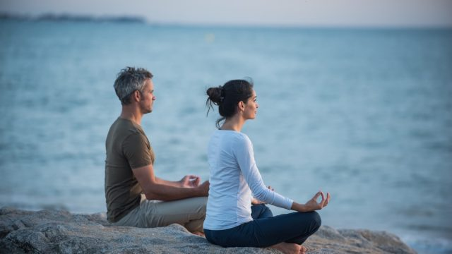 couple doing yoga at dawn on a beach