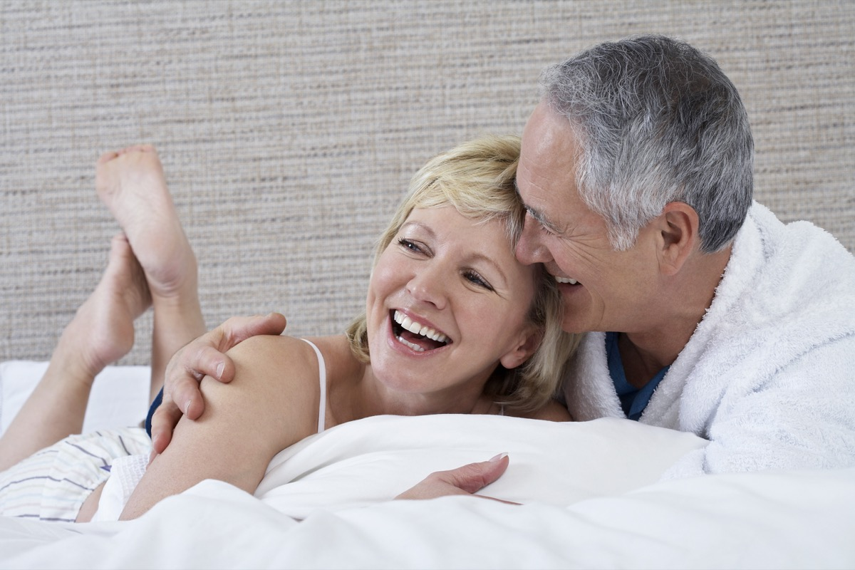 couple laughing in bed, healthy sex after 40