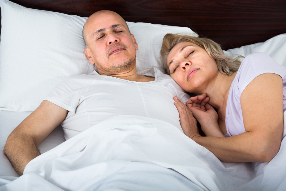 couple sleeping in bed together, smart person habits