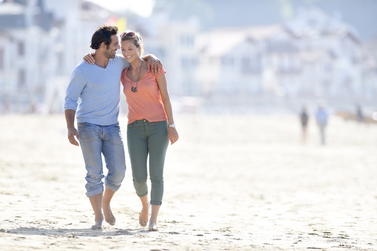 middle-aged couple walking on a beach with arms around each other