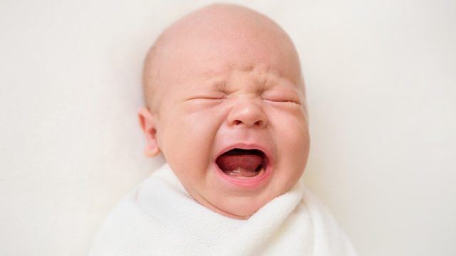 crying newborn baby in swaddle, parenting tips