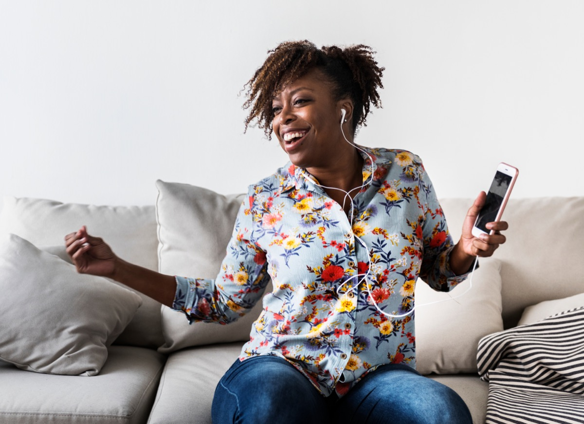 woman dancing alone listening to music with her headphones, stay younger