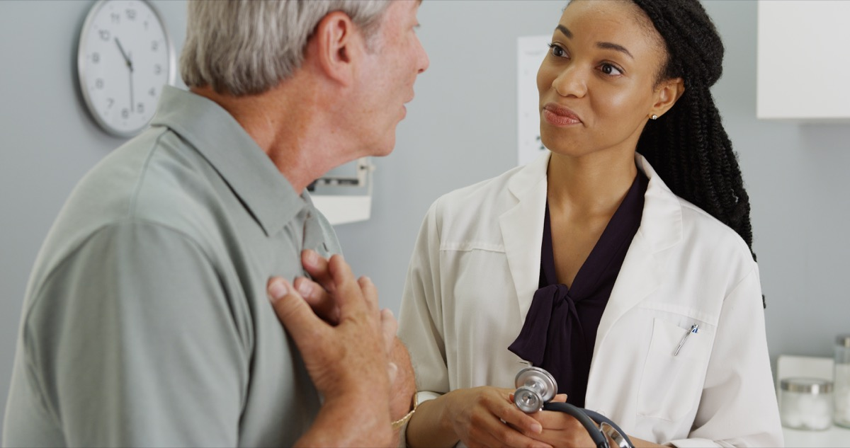 older man talking to young female doctor, heart health risks