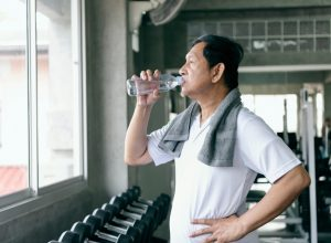 old man drinking water after exercising, ways to feel amazing