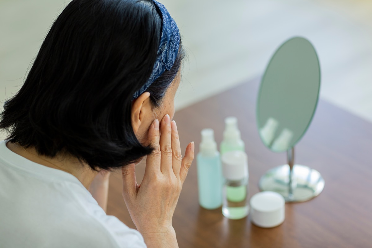 older woman looking at her dry skin, look better after 40
